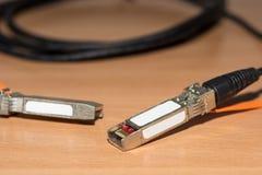 指挥10 Gb最快速度互联网的附上在木书桌上的铜电缆和网络 免版税图库摄影