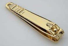 指甲夹特写镜头在金子颜色的 库存照片