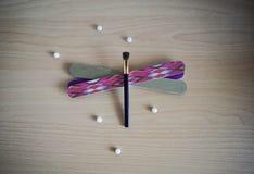 指甲锉眼影膏刷子蜻蜓形状和珍珠 免版税库存图片