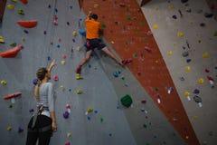 指示上升的墙壁的妇女运动员在健身俱乐部 免版税库存照片