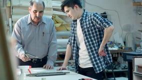 指示年轻实习生的资深男性工作者如何修建在书桌后的一个框架在框架车间 免版税库存照片