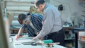 指示年轻实习生的资深男性工作者如何切开框架的一块玻璃在书桌后在框架车间 库存照片