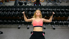 按与在健身房、运作的三头肌和胸口的哑铃的少妇长凳 影视素材