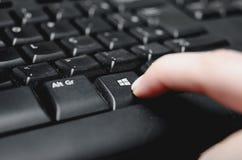 按从一个多灰尘的黑键盘的手指Windows键 库存图片