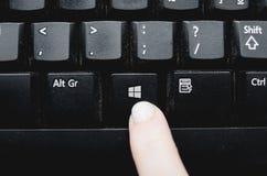 按从一个多灰尘的黑键盘的手指Windows键 免版税库存照片