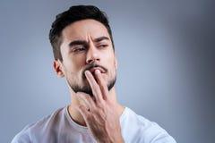 按他的两个手指的聪明的年轻人对嘴唇,当认为时 免版税库存图片