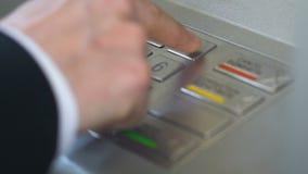 按商人的手插入私人密码和进入在ATM的按钮 股票视频