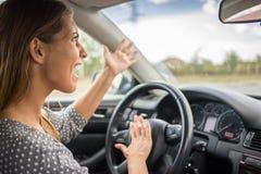 按喇叭在汽车的恼怒的妇女 免版税库存图片