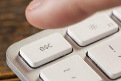 按在一个灰色键盘的手指逃命 库存照片