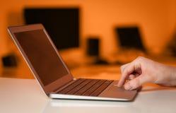 按在五颜六色的backgrou的商人现代便携式计算机 库存照片