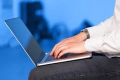 按在五颜六色的backgrou的商人现代便携式计算机 图库摄影