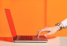 按在五颜六色的backgrou的商人现代便携式计算机 免版税图库摄影