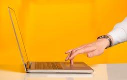 按在五颜六色的backgrou的商人现代便携式计算机 免版税库存照片