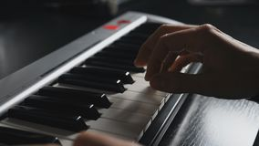 按在合成器钥匙的钢琴演奏家的手指 独奏使用音乐的人的手在钢琴 紧密慢动作顶视图 股票录像
