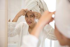按在她的前额的亚裔妇女粉刺 免版税图库摄影