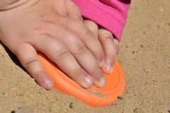 按在沙子的小女孩的手橙色pattypan形式 免版税库存照片