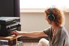 按在伴音系统佩带的耳机的妇女按钮 库存照片