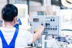 按在CNC机器的工作者按钮在工厂 免版税图库摄影
