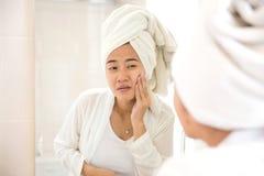 按她的面孔的年轻亚裔妇女,尝试取消粉刺 库存图片