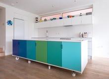 按客户需要设计的厨房在工业铸工轮子,在蓝色和绿色绘的减速火箭的设计的开放学制厨房里 库存图片