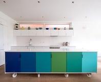 按客户需要设计的厨房在工业铸工轮子,在蓝色和绿色绘的减速火箭的设计的开放学制厨房里 库存照片
