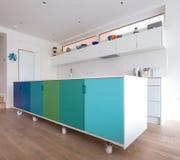 按客户需要设计的厨房在工业铸工轮子,在蓝色和绿色绘的减速火箭的设计的开放学制厨房里 免版税库存照片