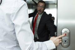 按按钮的女实业家电梯 商人被混淆的设法停止电梯 图库摄影