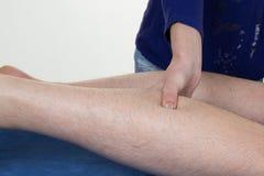 按摩人的小牛肌肉的手 施加在男性腿的女性治疗师压力 免版税库存照片