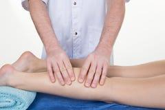 按摩人的小牛肌肉的治疗师 施加在女性腿的治疗师压力 免版税库存图片