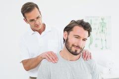 按摩内容的男性治疗师供以人员肩膀 库存图片