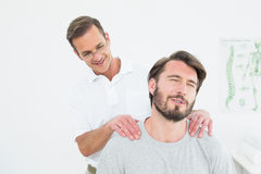 按摩内容的男性治疗师供以人员肩膀 免版税库存图片