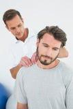 按摩内容的男性治疗师供以人员肩膀 免版税库存照片