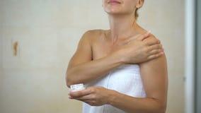 按摩和应用水合作用化妆水的中间年迈的妇女于身体在卫生间里 股票视频
