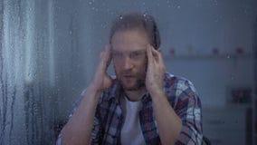 按摩在多雨窗口后的沮丧的人寺庙,遭受头痛 股票录像