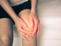 按摩她痛苦的膝盖的黑白少妇 库存图片
