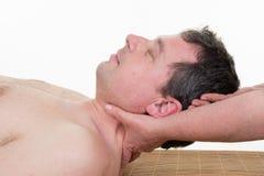 按摩妇女的脖子的女性治疗师,当拿着她的头在屋子里时 免版税图库摄影