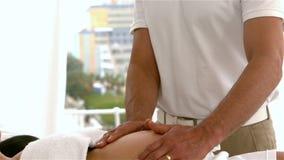 按摩孕妇的腹部的男性治疗师 影视素材