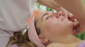 按摩年轻白肤金发的客户的面孔豪华沙龙的女性美容师 股票录像