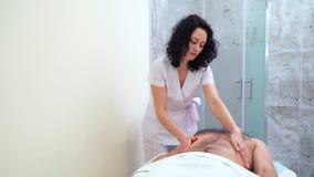 按摩男性顾客的肩膀和腹部的美丽的女性治疗师 影视素材