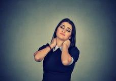 按摩紧张的脖子的疲乏的妇女 免版税库存照片