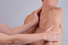 按摩脊柱治疗者,整骨疗法,镇痛概念 做在人后面的背部操作治疗师医治用的治疗 免版税图库摄影