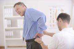 按摩脊柱治疗者:审查老人的按摩医生 库存照片