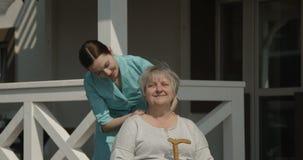 按摩资深妇女的生理治疗师在医院好日子射击的康复中心户外在红色照相机 股票录像