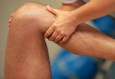 按摩运动员的大腿的手在跑以后 库存图片