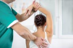 按摩医生按摩女性耐心脊椎和后面 库存图片