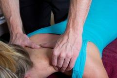 按摩医生按摩她的肩膀的患者 库存照片