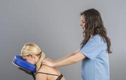 按摩医生,审查她的患者后面和做12月的生理治疗师 免版税库存图片