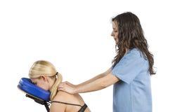 按摩医生,审查她的患者后面和做12月的生理治疗师 库存照片