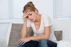 按摩头的妇女,当遭受头疼时 免版税库存图片