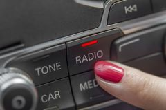 按汽车收音机立体声盘区和现代仪表板设备的女孩 免版税库存图片